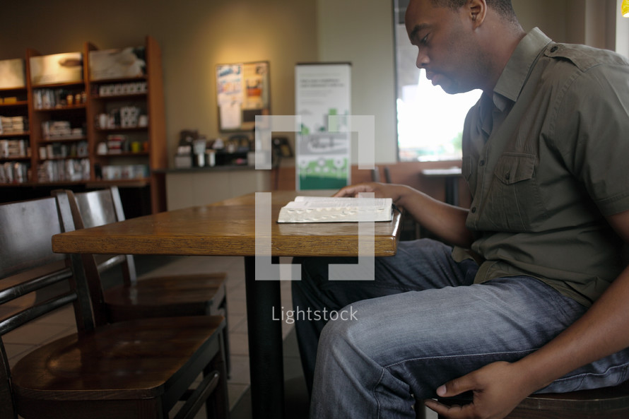 Man reading the Bible in a coffee shop.