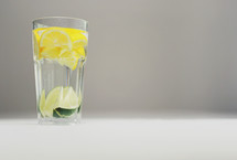 lemon and limes in a glass of water