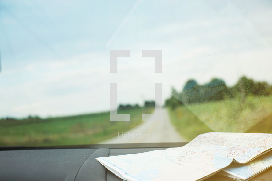 A road map on the dashboard of a car with a country road in front.