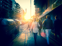 A group of people walking on a city pavement into strong direct sunlight. Cross-processed look.