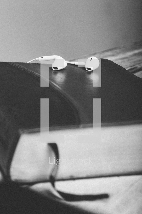 Ear buds on top of closed Bible laying on wooden table.