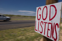 """God Listens"" sign nailed to a post on the side of the road."