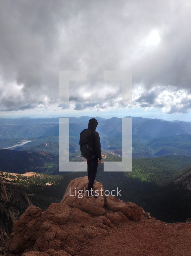 A man standing on a rock looking out over a valley