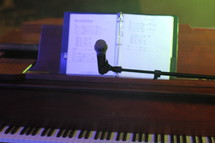 Music notes and microphone at a piano.