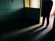 man and his shadow in a doorway