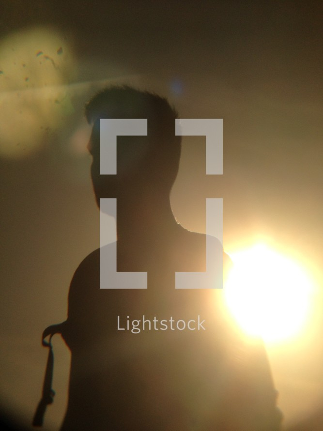 silhouette of a man and intense sun flare