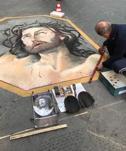 street artist painting Jesus on a sidewalk