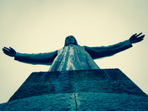 A shot from the persective of standing at the feet of a large stone statue of Jesus with arms outstreched. Cross-processed look.