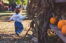 a toddler boy at a pumpkin patch