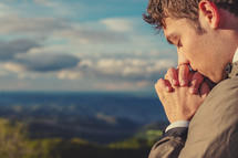 Christian worship and praise. A young man is praying on a mountaintop