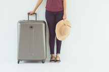 a woman standing with a sunhat and suitcase