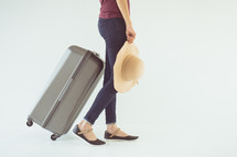 a woman with a sunhat carrying a suitcase