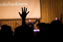 silhouettes of raised hands during a worship service,