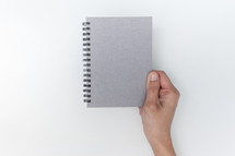 hand holding a silver notebook