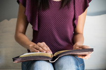 a teen girl reading a Bible in her lap
