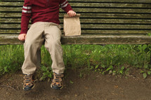 a child with a brown lunch bag sitting on a bench