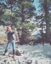 man with a shotgun in a snowy forest