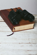 Binoculars on closed Bible laying on top of wooden table.