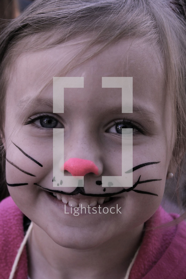 A little girl with face painted like a bunny