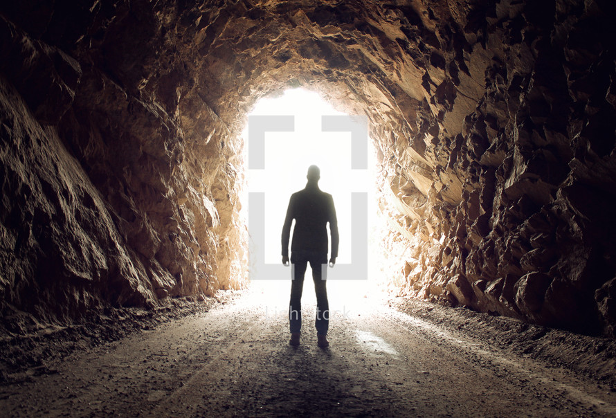 a man standing in a tunnel with light