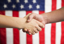 A handshake in front of an American flag.