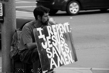 "Street preacher holding a ""Jesus Saves"" sign on the street corner."
