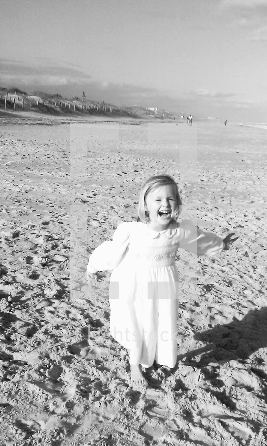 A happy little girl in a dress running on a beach carefree