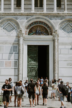 Tourists going in and out of the entrance to an ornate cathedral.