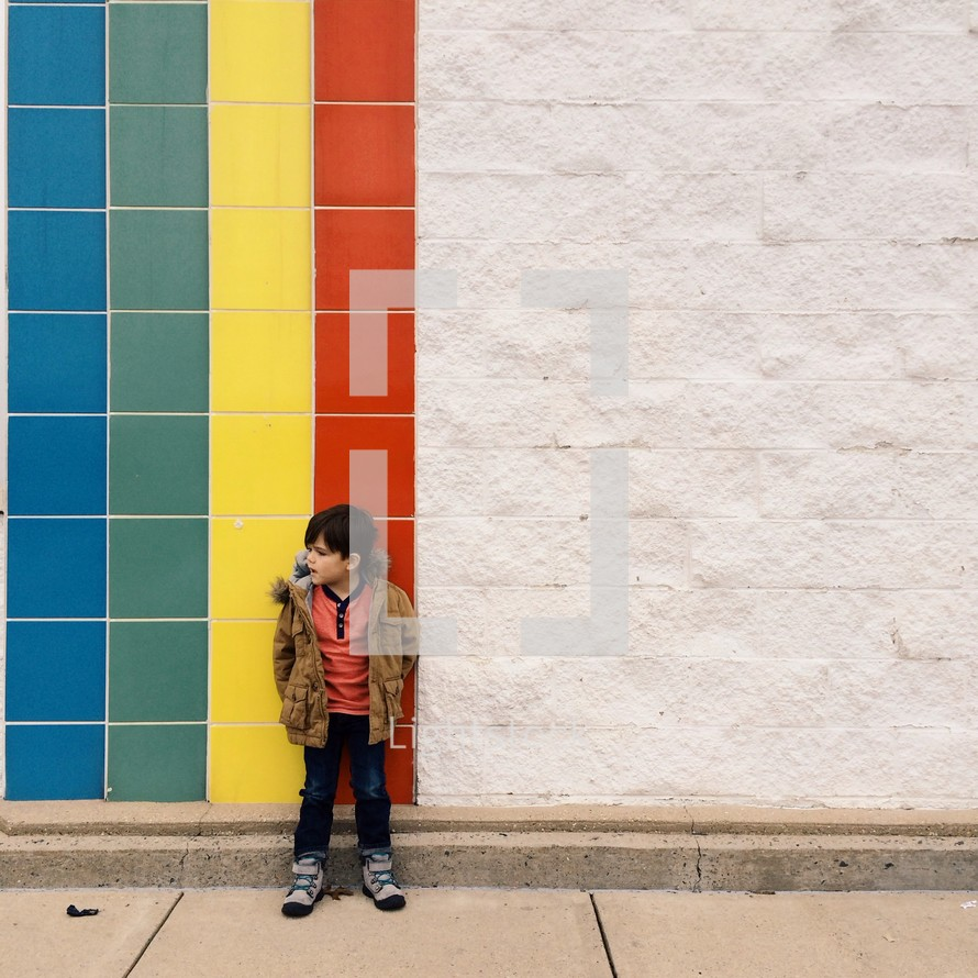 little boy standing in front of a rainbow tile wall.