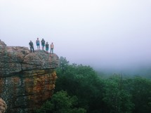 Family standing on a cliff above the tree tops.