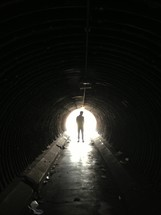 man walking towards the light in a tunnel