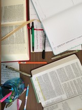Bibles, pens, journals, and highlighters scattered on a table