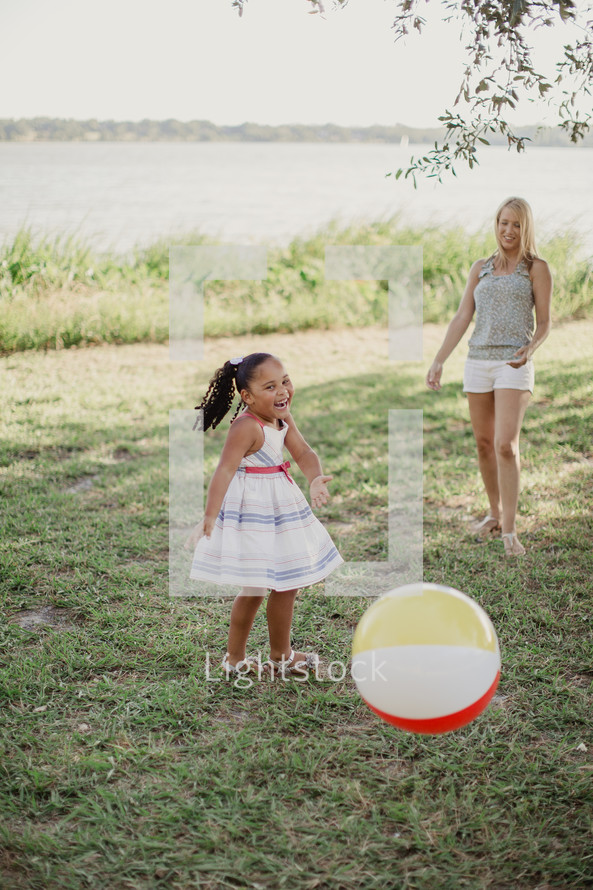 A little girl and woman laughing as they toss a beach ball.
