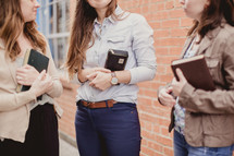 a group of young women holding Bibles