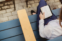 women reading Bibles while sitting on a park bench