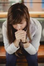 a young woman with head bowed in prayer