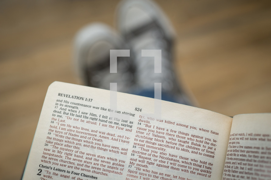 man reading Revelations in a Bible
