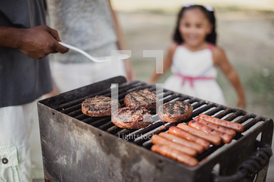 A little girl watches a man cooking hamburgers and hot dogs on an outside grill.