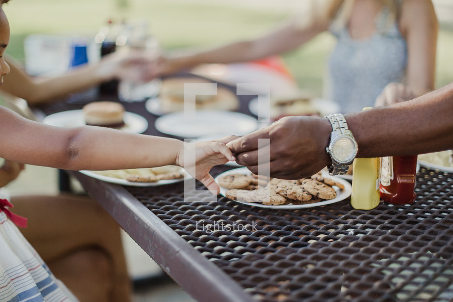 family holding hands in prayer at a picnic table outdoors