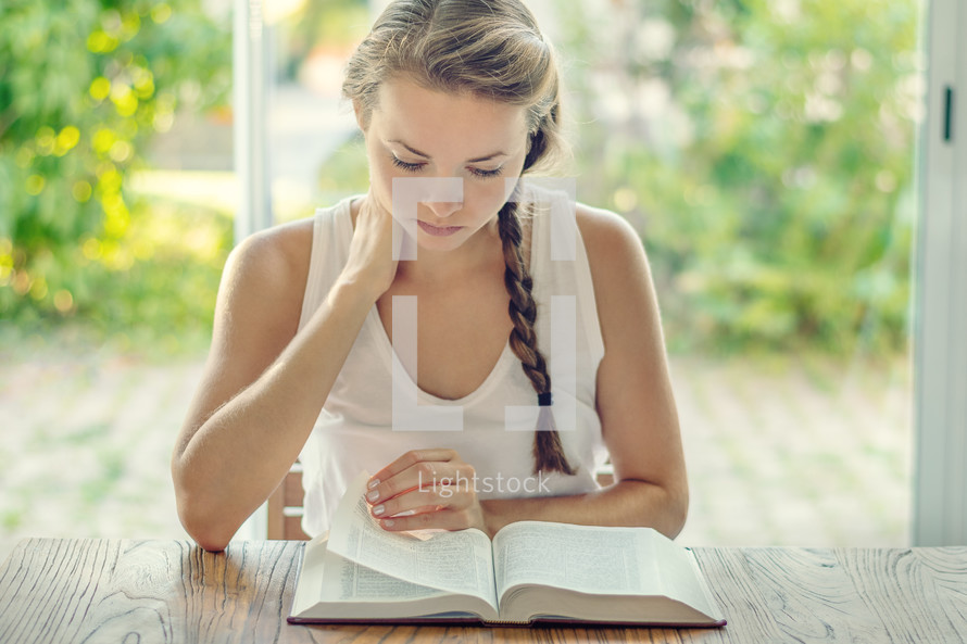 a young woman sitting reading a Bible