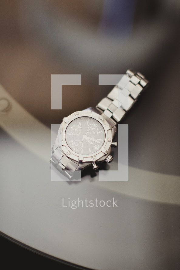 A watch rests on a glass table.
