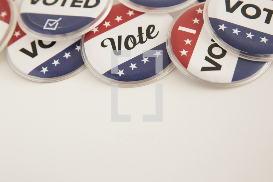 """Red, white and blue buttons reading, """"Vote,"""" and """"I Voted."""""""
