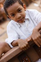 A boy climbing over a railing.