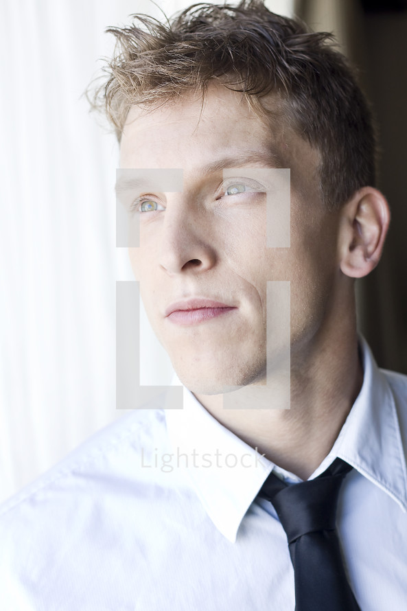 Man in shirt and tie looking out the window.