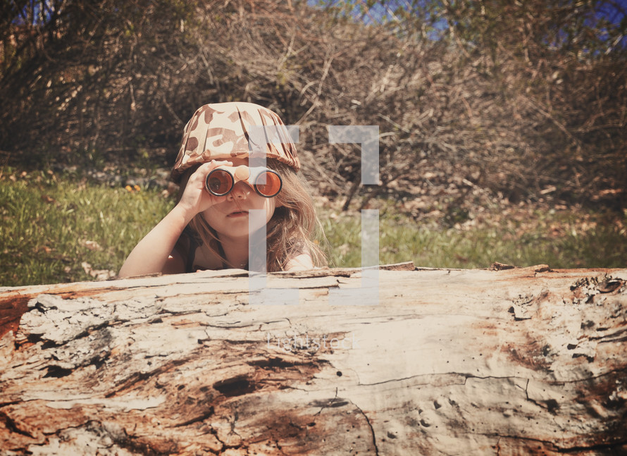 a little girl in camouflage with binoculars