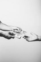 Two hands giving money to one hand.
