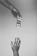 Hand reaching for $100 bill dangling from above.