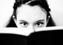 eyes of a teen girl reading a Bible in amazement
