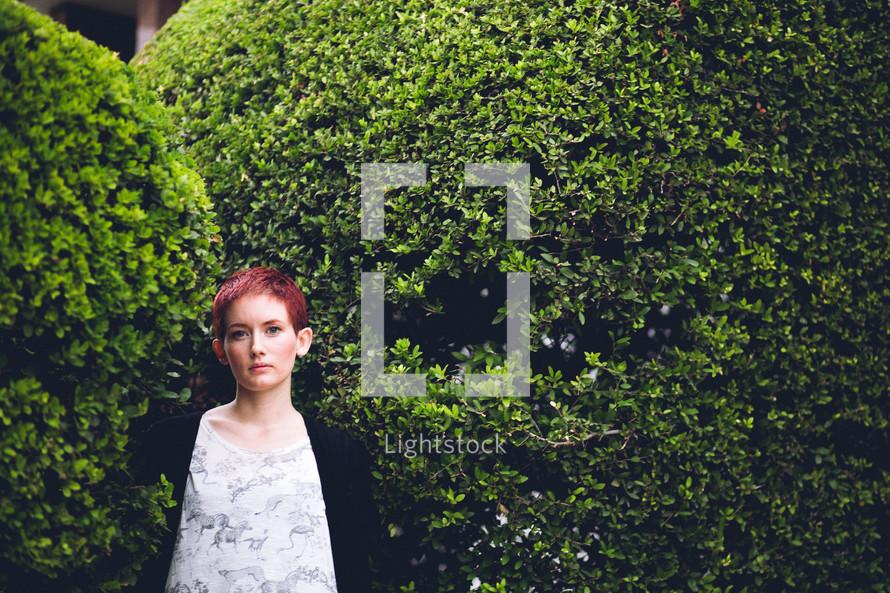 A woman standing in a garden.