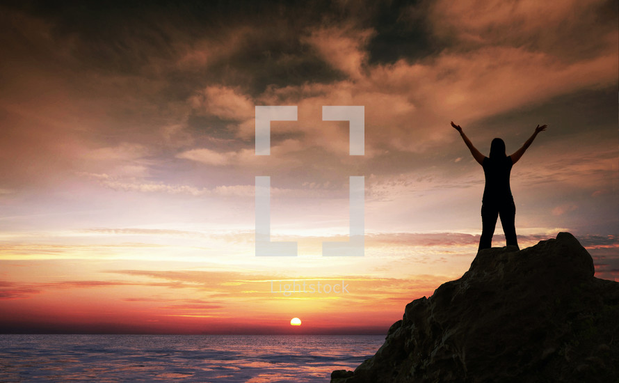 silhouette of a woman standing on a rock in front of the ocean at sunset with her hands raised in worship to God